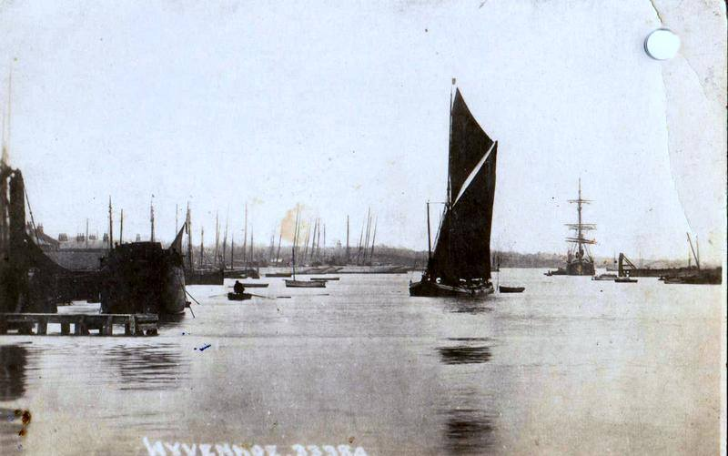A black and white photograph of the River Colne at Wivenhoe. A Thames barge in full sail is in the middle of the photograph; a square rigger is to the right in the distance. On the left, the masts of many boats can be seen, and a jetty is in the foreground.