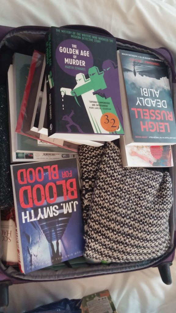 A suitcase full of books, with a jumper that just happened to be there.
