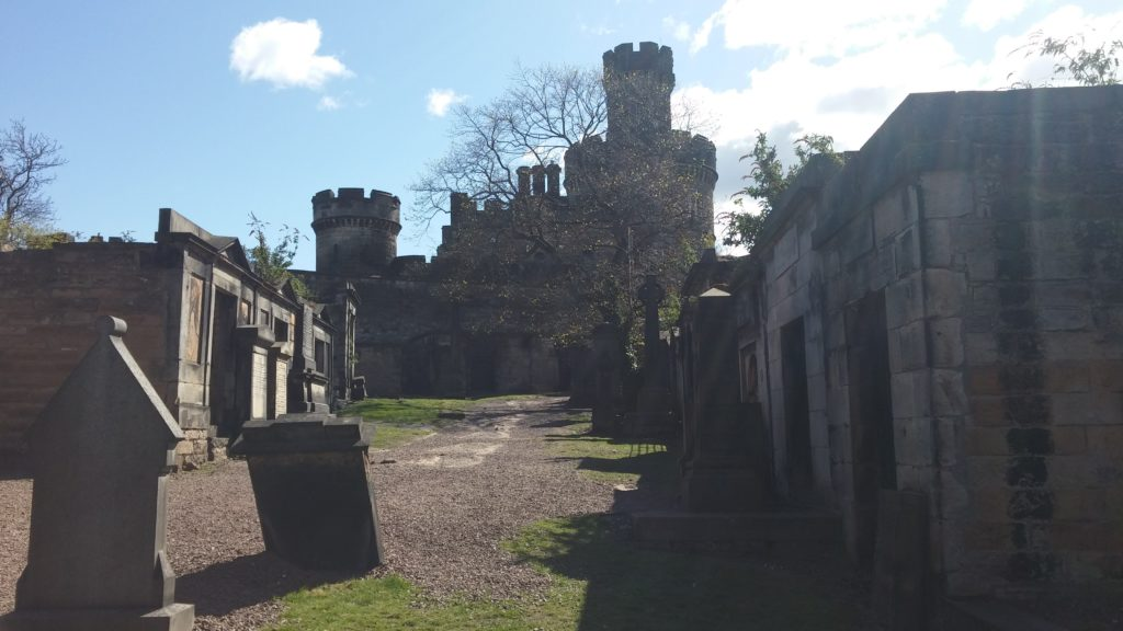 Graves and a castle at Old Calton cemetery, beneath a blue sky