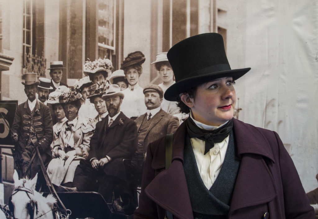 Me in a top hat, trying to look like a Victorian professor, in front of a large sepia print photo of a street scene
