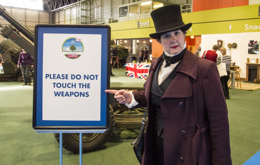 "Me in costume, stern of face, pointing to a sign saying ""Please do not touch the weapons."" In the background, you can just about see some items of WW2 military hardware."