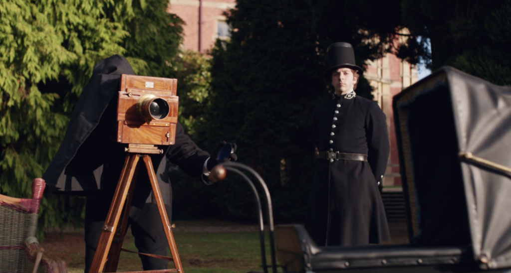 A Victorian camera is set up to take a photograph of a pram. A Victorian policeman looks on.