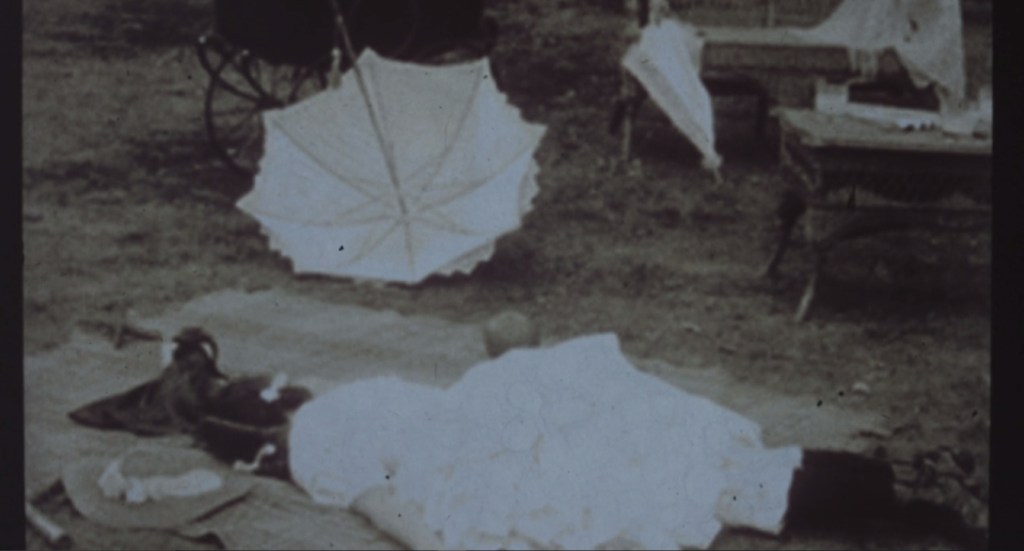 A Victorian child lies on the ground, an upturned parasol nearby. She could be asleep, but we're told this is a crime scene photo following a shocking murder.