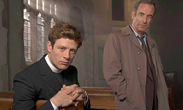 A vicar is seated in a pew with a plain-clothes detective in a brown raincoat standing beside him. They are in a church and light pours in through a window behind them.