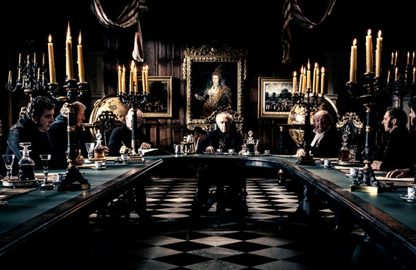 A grand room with scary looking men sitting around a table.