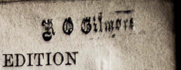 A stamp in faux Gothic lettering, saying R O Gilmore.