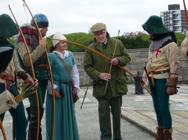 Robert Hardy in a flat cap shows a bow to historical re-enactment people in Mediaeval costume.