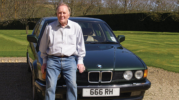 Actor Robert Hardy stands in front of a BMW car with the registration plate 666 RH