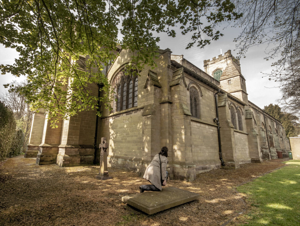 The back of the church, with what remains of the Palmer family grave, with an author in a mac carefully kneeling on it.