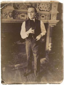 Dressed in mid-19th C costume, Jonathan Goodwin stands in front of an elaborate carved stone fireplace.