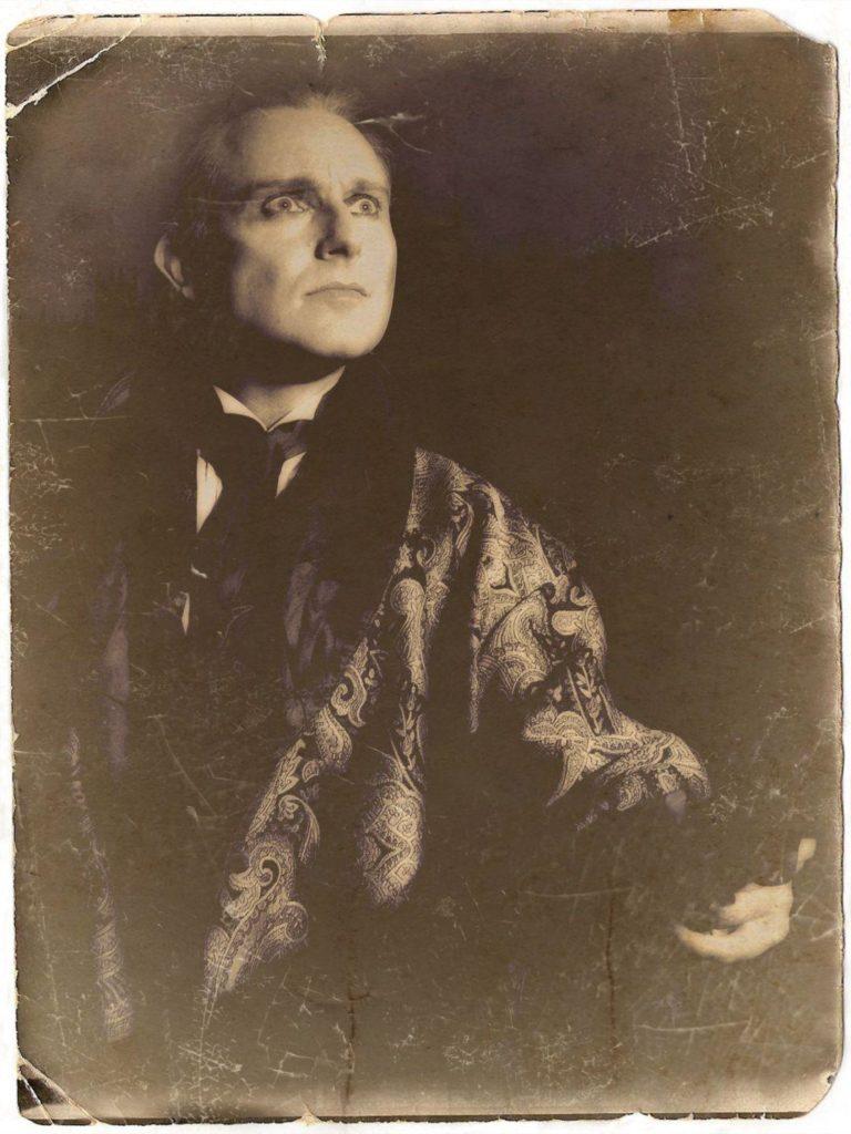 Jonathan Goodwin as Sherlock Holmes, in smoking jacket.