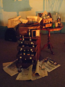 The set for Murder by Gaslight. A wooden chest with drawers filled with antique poison bottles, a table beside it with more bottles, and on the floor scattered about newspapers reporting poisoner trials.
