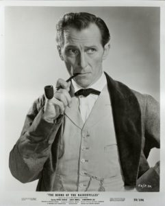 "Peter Cushing as Sherlock Holmes in ""The Hound of the Baskervilles"", smoking a pipe."